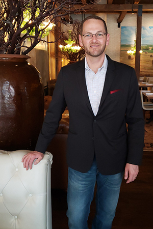 Man in blue suit jacket with button-down shirt standing in dining room.