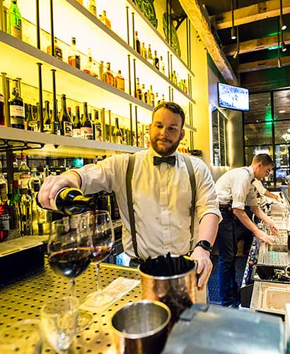 Bartender pouring glass of red wine behind bar with wall of spirits behind him.